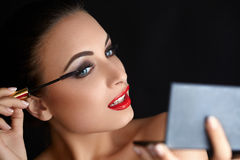 Portrait of young woman applying mascara.  Mascara Brush. Red Li Stock Image