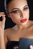 Portrait of young woman applying mascara.  Mascara Brush. Red Li Royalty Free Stock Photos