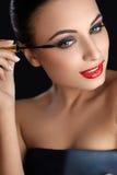 Portrait of young woman applying mascara.  Mascara Brush. Red Li Stock Photos