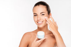 Portrait of young woman applying moisturizer cream on her face. Isolated on white background Royalty Free Stock Images
