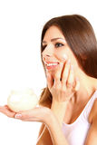 Portrait of young woman applying moisturizer cream on her pretty Royalty Free Stock Image
