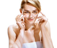 Portrait of young woman applying moisturizer cream on her pretty face. Stock Photos