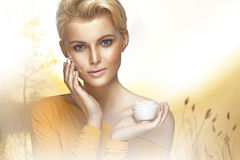 Portrait of young woman applying moisturizer cream Stock Photography
