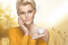 Portrait of young woman applying moisturizer cream Royalty Free Stock Images
