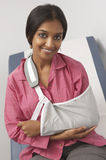 Portrait Of Young Woman With Arm In Sling. Portrait of a smiling Indian female with arm in sling royalty free stock image