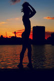 Portrait of young woman as silhouette by the river. Slim sporty girl is posing in river embankment in front of red Stock Photo