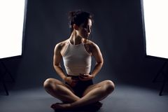 Young woman athlete in black high-waist panties and white top sitting in lotus position on the floor between two studio flashes. Portrait of young woman athlete Stock Photos