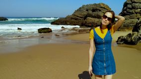 Portrait of young woman on Atlantic ocean sandy beach Portugal. Portrait of young woman on Atlantic ocean sandy beach in jeans dress in Portugal stock footage