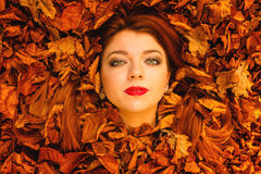 Portrait of young woman in autumn leaves. Royalty Free Stock Photos