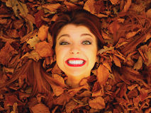 Portrait of young woman in autumn leaves. Stock Photography