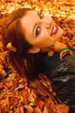 Portrait of young woman in autumn leaves. Royalty Free Stock Photography