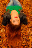 Portrait of young woman in autumn leaves. Royalty Free Stock Image