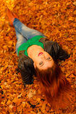 Portrait of young woman in autumn leaves. Royalty Free Stock Photo