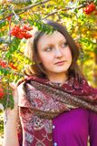 Portrait of young woman in autumn park. Portrait of young woman on background of mountain ash in park stock photography
