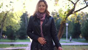 Portrait of young woman in autumn Park. the girl in the scarf and coat playfully turns and looks at the camera. Young beautiful woman walking on autumn park stock video