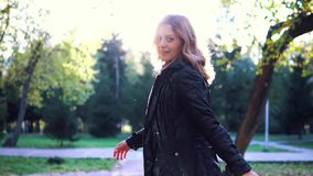 Portrait of young woman in autumn Park. the girl in the scarf and coat playfully turns and looks at the camera. slow. Young beautiful woman walking on autumn stock video