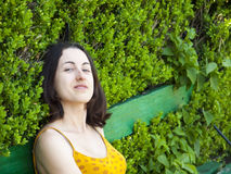 Portrait of a young woman on a background of green leaves. Royalty Free Stock Photography