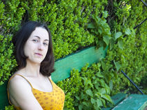 Portrait of a young woman on a background of green leaves. Royalty Free Stock Image