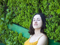 Portrait of a young woman on a background of green leaves. Stock Photography