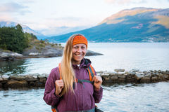 Portrait Young woman with backpack on fjord coast royalty free stock images