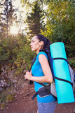 Portrait of a young woman backpacker with backpack in forest, profile Royalty Free Stock Photo