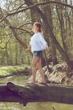 Portrait of a young woman balancing on fallen tree trunk across stream Stock Images