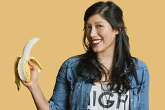 Portrait of a young woman with banana over colored background Stock Images