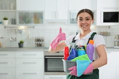 Portrait of young woman with basin of detergents. Cleaning service royalty free stock images