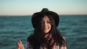 Portrait of a young woman on the beach. girl in hat and autumn coat smiling and posing on camera by the water. Slow stock video footage