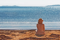 Portrait of young woman on the beach near the sea sitting wearin Royalty Free Stock Images