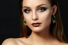 Portrait of young woman with beautiful makeup. Close up portrait of young woman with brown lips and green smokey eyes over black background. Perfect eyebrows Stock Photos
