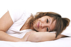 A portrait of a young woman in bed. A young, happy caucasian woman rests in bed.  Set against a white background Royalty Free Stock Photos
