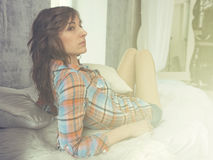 Portrait of young woman in bed dressed casual shirt, Sun Light, toned, warm colors Stock Photography