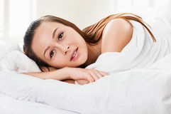 Portrait of the young woman in bed on pillow Stock Photo