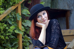 Portrait of a young woman in black hat with an enigmatic smile Royalty Free Stock Photos