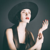 Portrait of young woman in a black hat. Studio photo young woman in black with graphic quality lighting Stock Photos