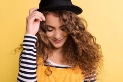 Portrait of a young woman with black hat in a studio on a yellow background. A portrait of a young woman with black hat and yellow dress in a studio on a yellow stock photos