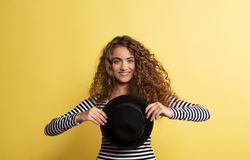 Portrait of a young woman with black hat in a studio on a yellow background. A portrait of a young woman with black hat in a studio on a yellow background royalty free stock image