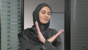 Portrait of Young woman in black hijab showing stop sign, Dislike, Rejecting Gesture, Disagree Sign, Crossing hands 60. Fps 4k stock video footage
