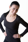 Cheerful brunette girl standing with arms on hips Stock Images