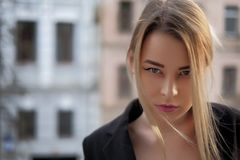 Portrait of a young woman in a black suit close-up against a background of a blurry city in the rays of the setting sun. Royalty Free Stock Photography