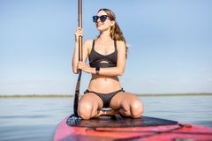 Woman on the paddleboard. Portrait of a young woman in black swimsuit sitting on the paddleboard no the lake royalty free stock photography