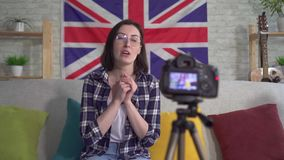Portrait young woman blogger in shirt on the background flag of great Britain recording video. Portrait young woman blogger in shirt and glasses on the stock video