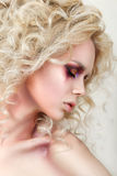 Portrait of young woman with blond curly hair and fashion make-u Royalty Free Stock Photography