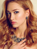 Portrait of young woman with blond curly hair wears luxurious bijou Stock Image