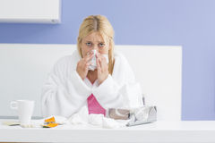 Portrait of young woman blowing nose in tissue paper Stock Photography