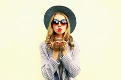 Portrait young woman blowing red lips sending air kiss in round hat royalty free stock photography