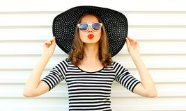 Portrait young woman blowing red lips sending sweet air kiss in black summer straw hat on white wall. Background royalty free stock photos