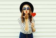 Portrait young woman blowing red lips sending sweet air kiss with red heart shaped lollipop in black round hat on white wall. Background royalty free stock photo