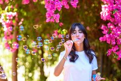 Happy beautiful young woman blowing soap bubbles outdoor. royalty free stock image